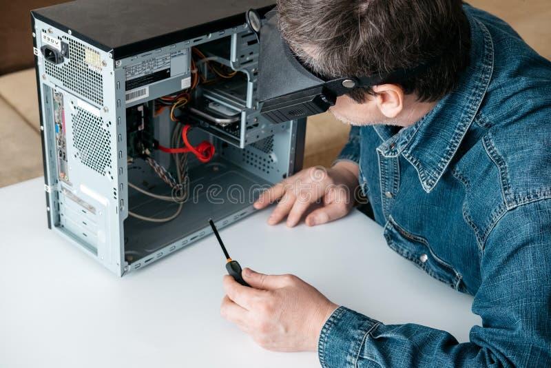 O reparador está desmontando o computador pessoal O coordenador é PC quebrado diagnóstico e fixando na oficina imagens de stock