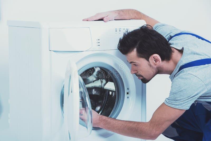 O reparador está reparando uma máquina de lavar no fundo branco fotografia de stock royalty free