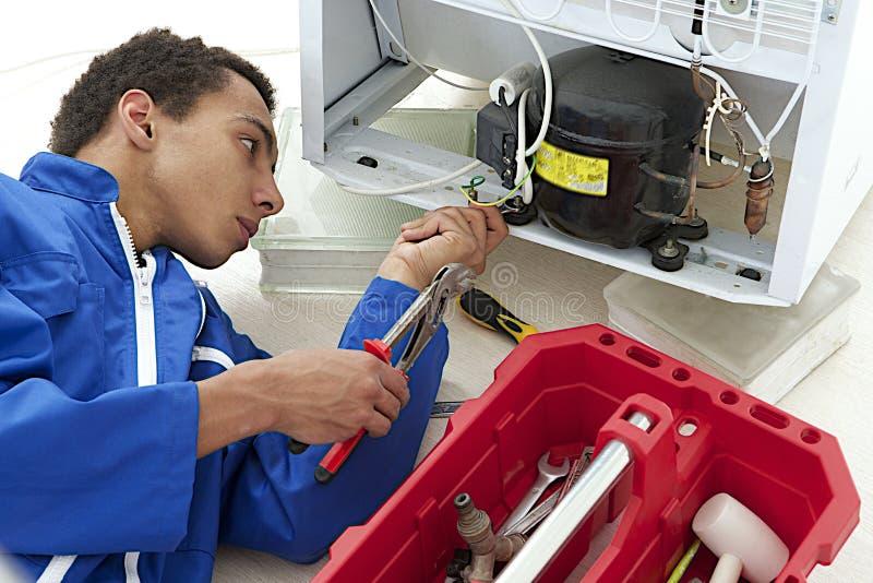 O reparador faz a pesquisa de defeitos e a manutenção do dispositivo do refrigerador imagens de stock royalty free