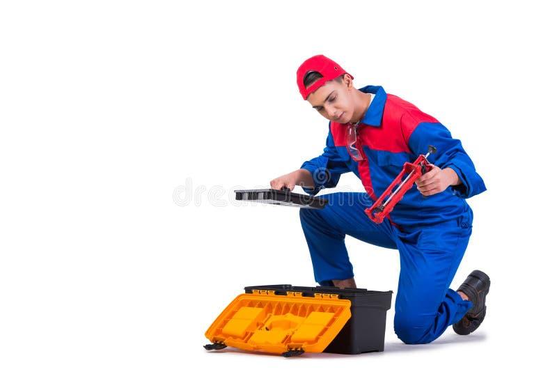 O reparador novo com a arma do silicone isolada no branco imagens de stock