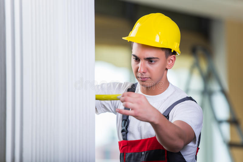 O reparador novo com a fita métrica que trabalha em reparos foto de stock