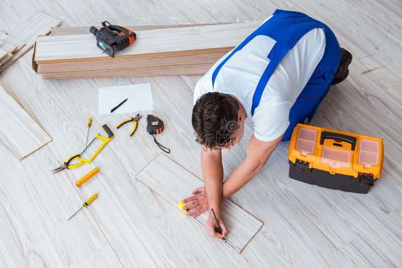 O reparador que coloca a pavimentação estratificada em casa fotos de stock royalty free