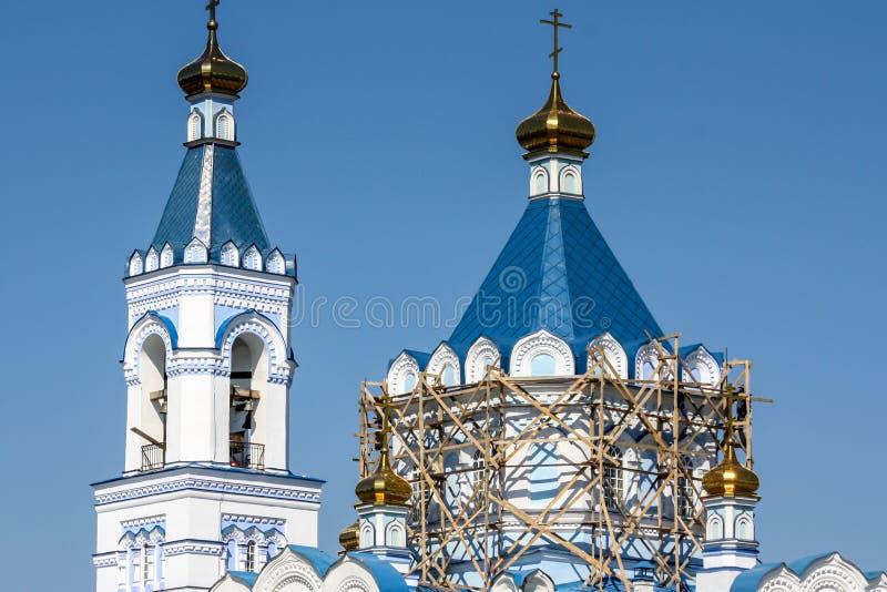 O reparo do andaime da igreja ortodoxa na torre, em um telhado azul e no céu azul imagens de stock