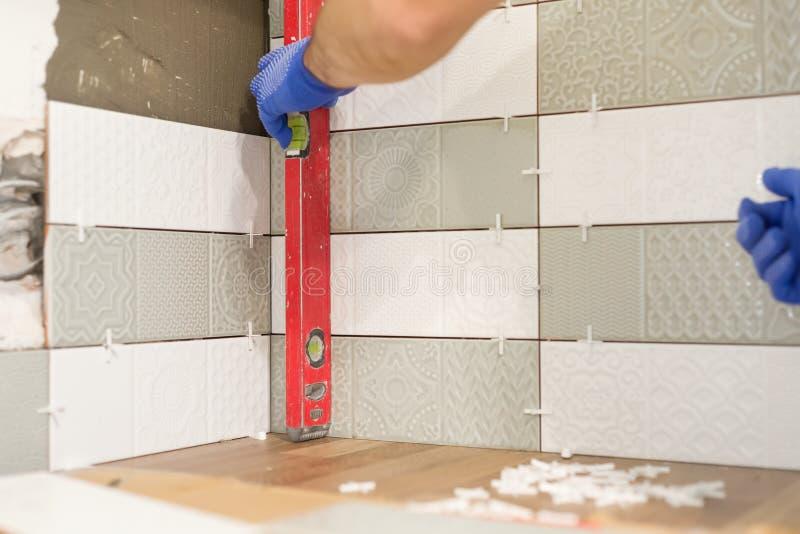 O reparo e a construção da cozinha, mãos do tiler que instalam azulejos na parede, usam ferramentas profissionais, colocação real fotos de stock royalty free