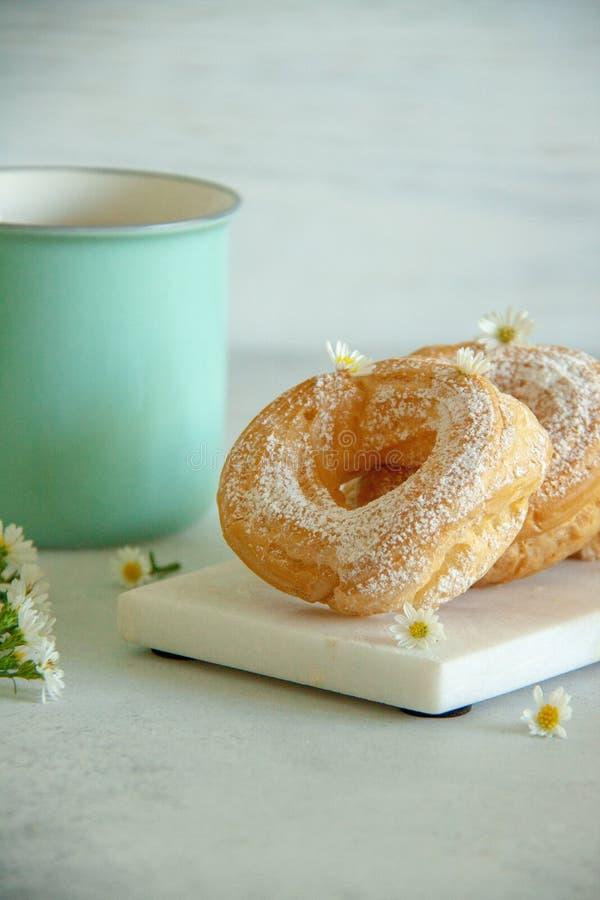 O requeijão soa em uma placa branca com as flores brancas pequenas e o copo de chá azul imagens de stock royalty free
