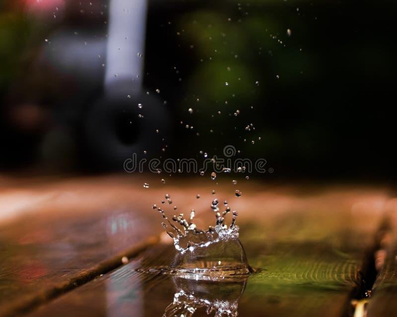 O respingo de uma gota da água em uma plataforma de madeira fotografia de stock royalty free