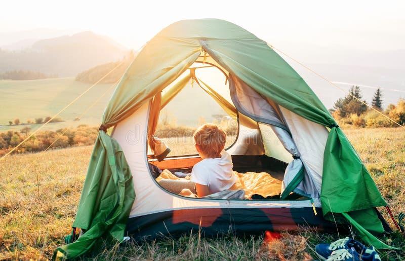 O resto do menino na barraca de acampamento e aprecia com luz do por do sol no vale da montanha imagens de stock