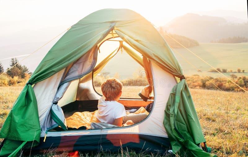 O resto do menino na barraca de acampamento e aprecia com luz do por do sol no vale da montanha imagem de stock royalty free