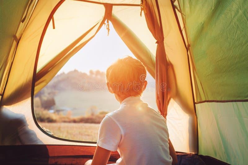 O resto do menino na barraca de acampamento e aprecia com luz do por do sol no vale da montanha imagem de stock