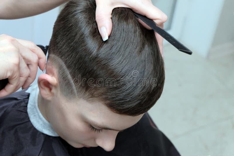 O resultado do trabalho de um cabeleireiro em um salão de beleza Corte de cabelo elegante com um teste padrão barbeado na cabeça  fotografia de stock royalty free
