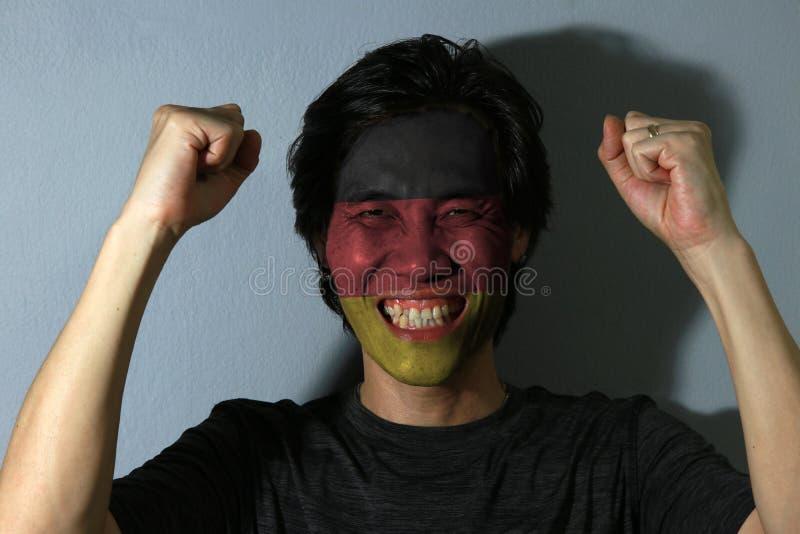 O retrato alegre de um homem com a bandeira de Alemanha pintou em sua cara no fundo cinzento imagens de stock royalty free
