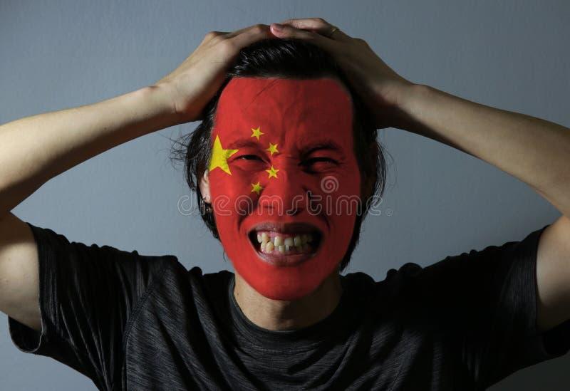 O retrato alegre de um homem com a bandeira da China pintou em sua cara no fundo cinzento O conceito do esporte ou do nacionalism foto de stock