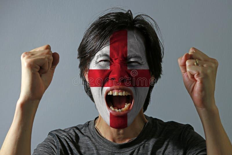 O retrato alegre de um homem com a bandeira da Inglaterra pintou em sua cara no fundo cinzento fotografia de stock royalty free