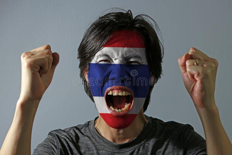 O retrato alegre de um homem com a bandeira da Tailândia pintou em sua cara no fundo cinzento imagens de stock