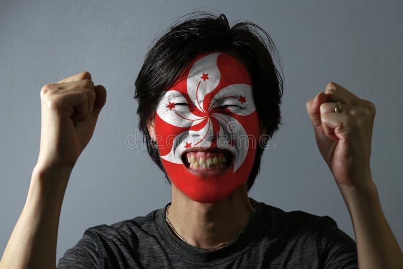 O retrato alegre de um homem com a bandeira do Hong Kong pintou em sua cara no fundo cinzento O conceito do esporte foto de stock royalty free