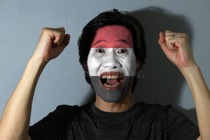 O retrato alegre de um homem com a bandeira de Iémen pintou em sua cara no fundo cinzento O conceito do esporte ou do nacionalism foto de stock