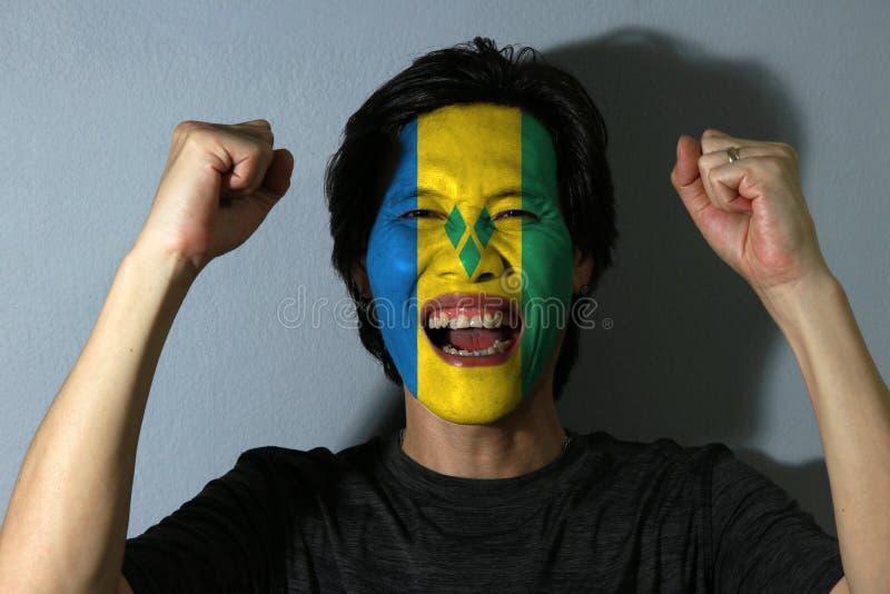 O retrato alegre de um homem com a bandeira de Saint Vincent pintou em sua cara no fundo cinzento O conceito do esporte ou do nac imagem de stock