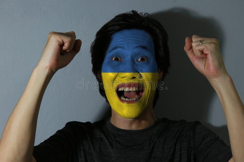 O retrato alegre de um homem com a bandeira de Ucrânia pintou em sua cara no fundo cinzento O conceito do esporte ou do nacionali imagem de stock royalty free