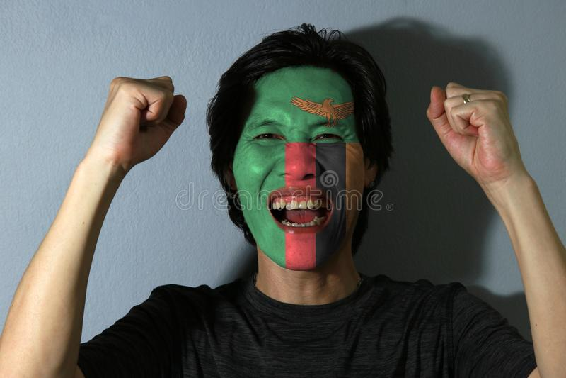 O retrato alegre de um homem com a bandeira de Zâmbia pintou em sua cara no fundo cinzento foto de stock royalty free