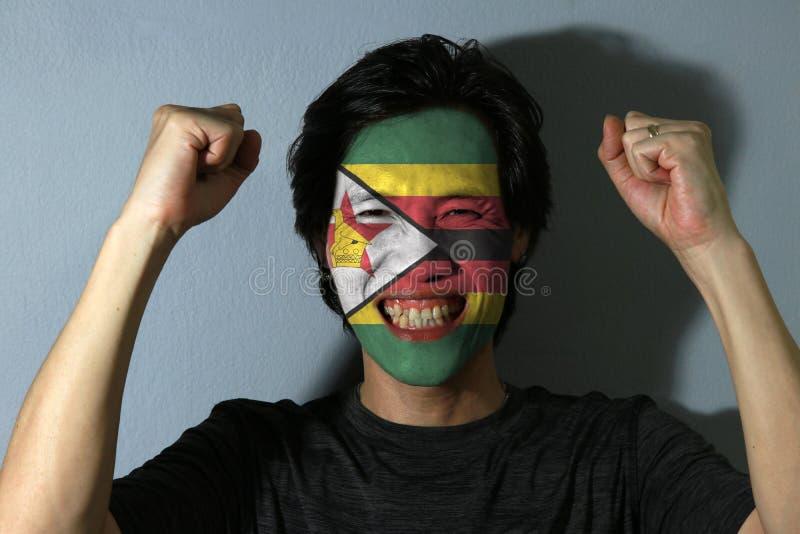O retrato alegre de um homem com a bandeira de Zimbabwe pintou em sua cara no fundo cinzento fotografia de stock