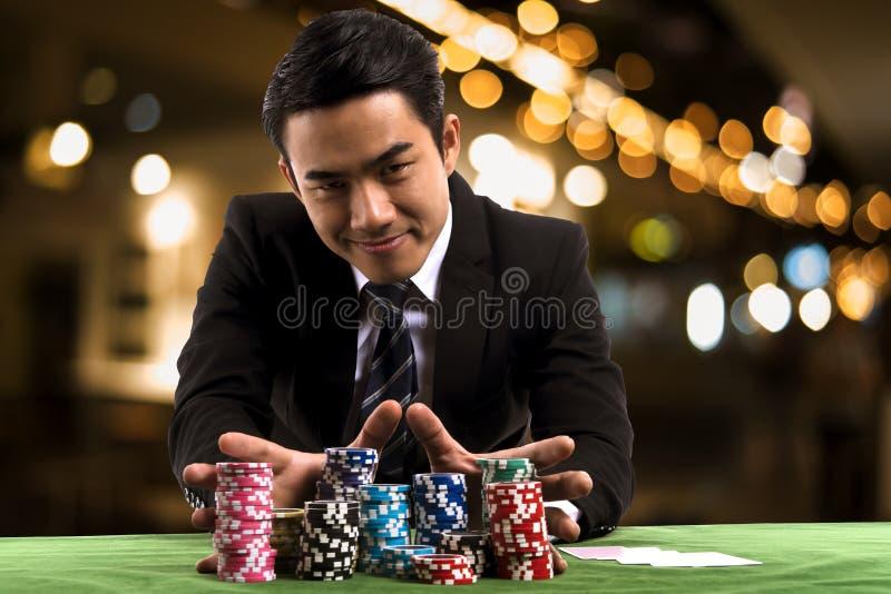 O retrato as mãos usadas do jogador de pôquer empurra microplaquetas da pilha para a frente para fotografia de stock royalty free