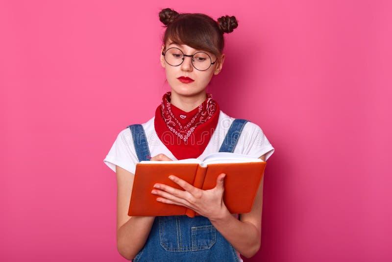 O retrato ascendente próximo da jovem mulher, adolescente atrativo com grupos guarda o caderno nas mãos, redige para baixo alguma imagens de stock