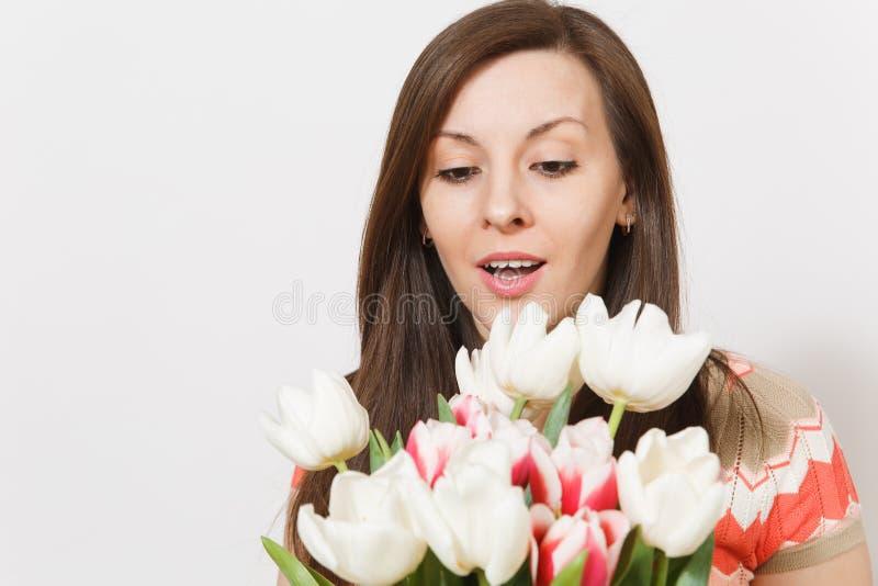 O retrato ascendente próximo da menina moreno nova bonita está guardando o ramalhete brilhante de branco e as tulipas cor-de-rosa foto de stock