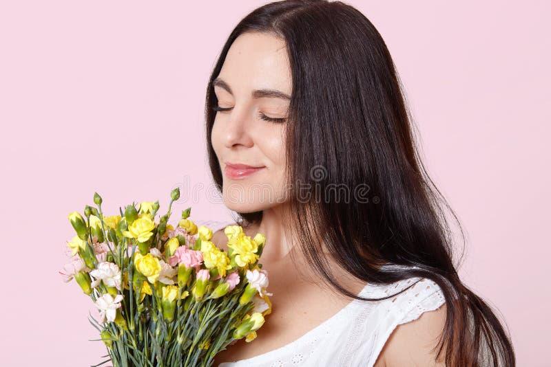 O retrato ascendente pr?ximo da posi??o ador?vel de cabelo preta da jovem senhora com olhos fechados, guardando flores adiantadas imagens de stock royalty free