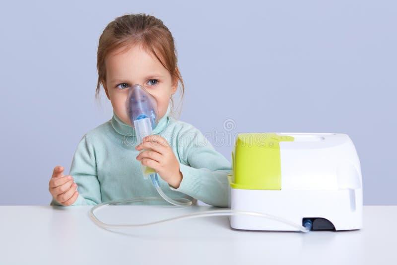 O retrato ascendente próximo de encantar a menina pequena bonito usa a máscara do nebulizer para o inahlation, tem a doença respi fotografia de stock