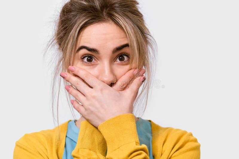 O retrato ascendente próximo do estúdio da boca horrorizada chocada da coberta da jovem mulher com mãos sente a vista assustado d foto de stock
