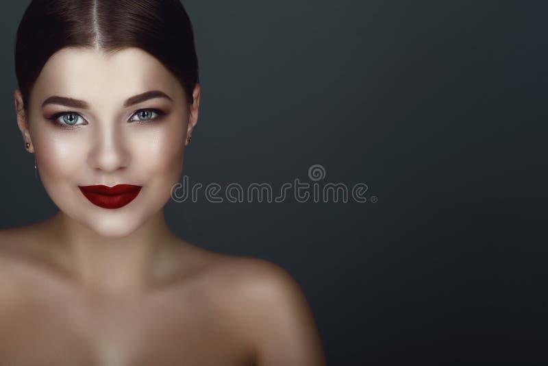O retrato ascendente próximo do modelo de cabelo escuro de sorriso bonito com perfeito compõe e centra o bolo lustroso da parte fotografia de stock