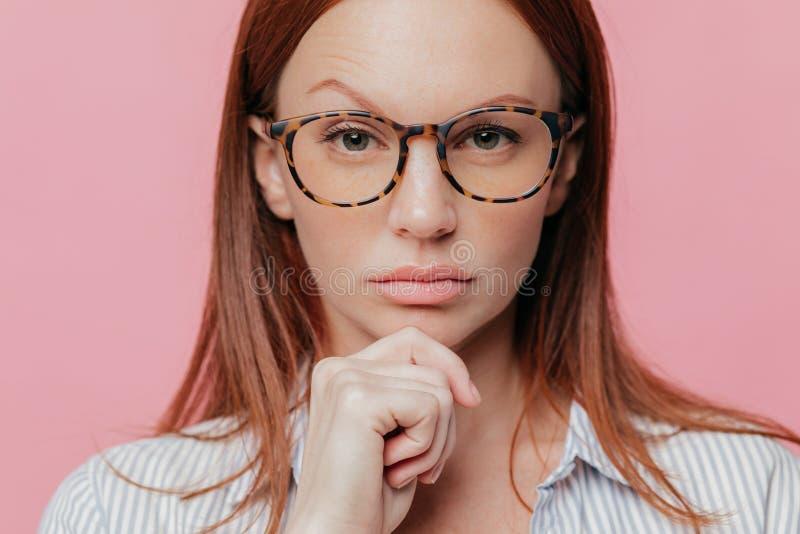 O retrato ascendente próximo do proprietário empresarial fêmea auto-confiante guarda o queixo, aumenta a sobrancelha, veste vidro fotografia de stock