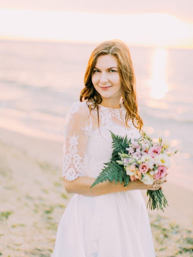 O retrato bonito da noiva de sorriso que guarda o ramalhete do casamento no fundo do por do sol imagens de stock