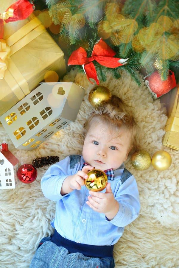 O retrato bonito do bebê pequeno comemora o Natal Feriados do ` s do ano novo O menino no boytie encontra-se sob a árvore, jogand fotografia de stock royalty free