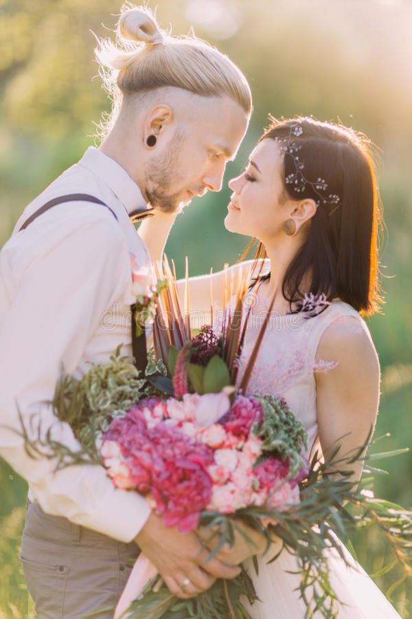 O retrato bonito do close-up dos recém-casados perto de se e guardando o ramalhete cor-de-rosa na floresta ensolarada fotos de stock