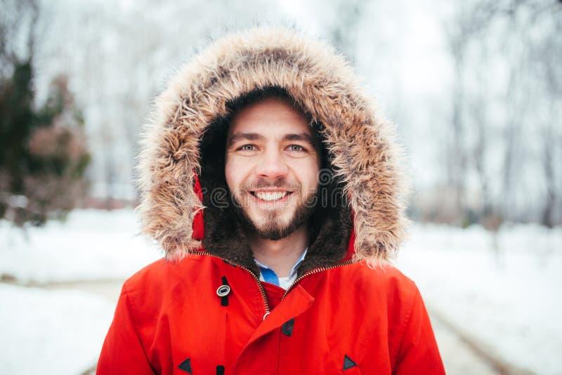 O retrato, close-up de um homem à moda vestido dos jovens que sorri com uma barba vestiu-se em um revestimento vermelho do invern imagens de stock royalty free