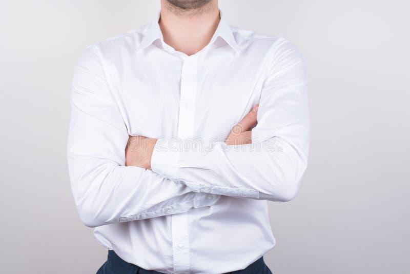 O retrato colhido da foto do close up do único cavalheiro macho sério que guarda as mãos de braços cruzou limpo claro vestindo co fotos de stock royalty free