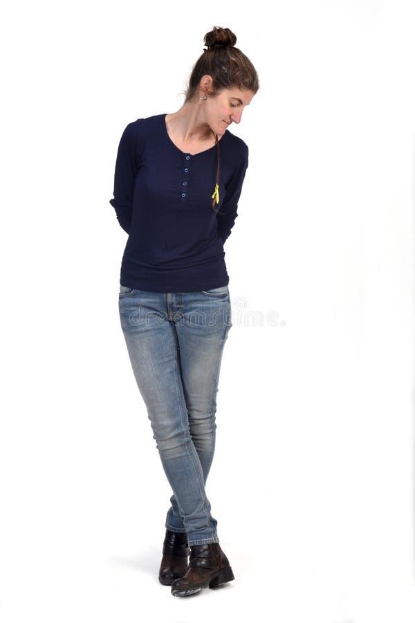 O retrato completo de uma mulher de meia idade que olham para baixo e dos pés cruzou-se fotos de stock