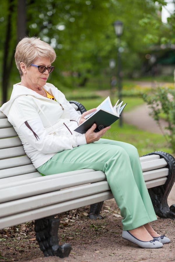 O retrato completo do comprimento da mulher superior nos vidros lê o livro no banco no parque imagem de stock