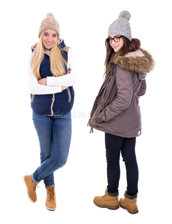 O retrato completo do comprimento de duas jovens mulheres no inverno veste o isolat fotografia de stock