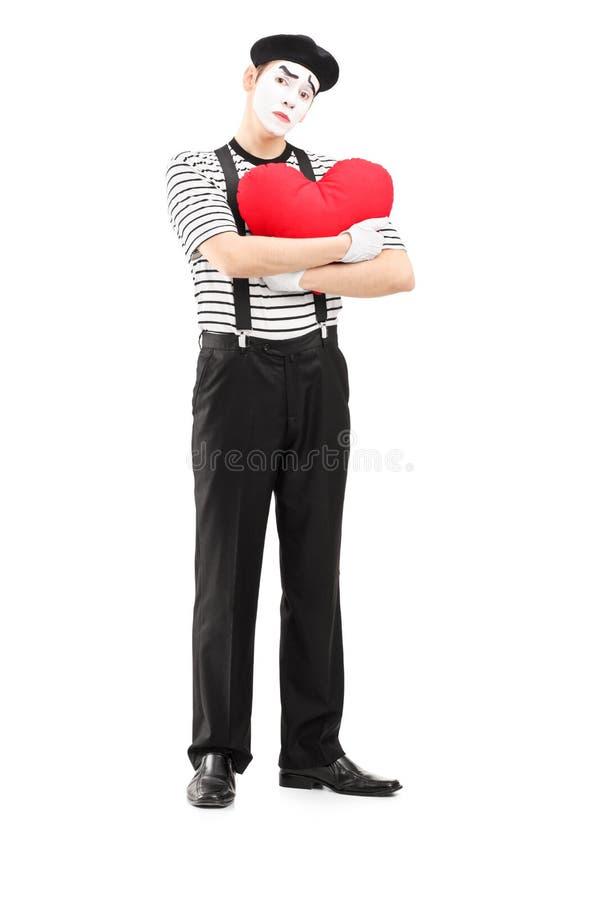 O retrato completo do comprimento de um triste mimica o artista que guardara um coração vermelho imagens de stock royalty free