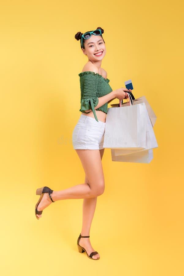 O retrato completo do comprimento de uma mulher atrativa alegre guarda o shoppi fotografia de stock