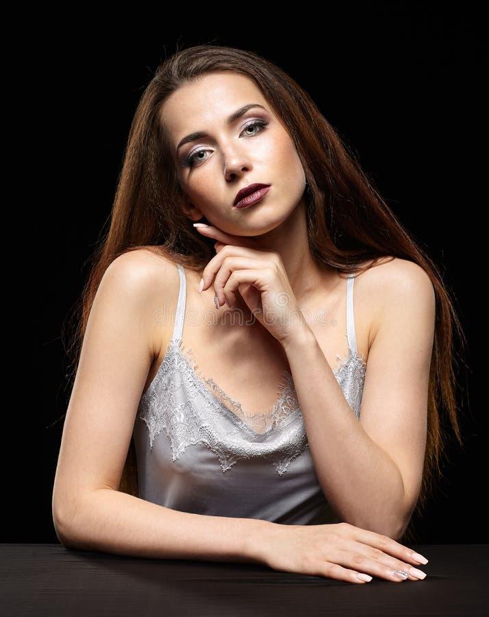 O retrato da beleza da jovem mulher senta-se na tabela preta Brunette fotos de stock