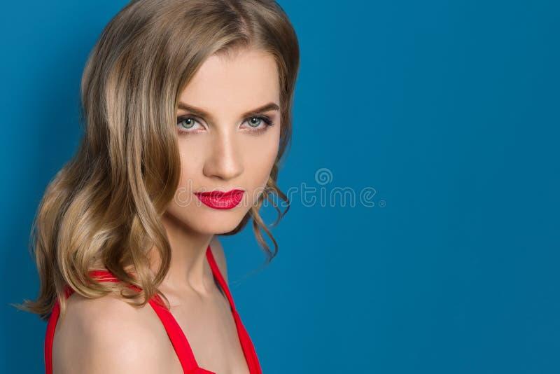 O retrato da beleza da mulher loura nova com os bordos vermelhos brilhantes, olhos azuis, no vestido vermelho no fundo azul, copi foto de stock royalty free