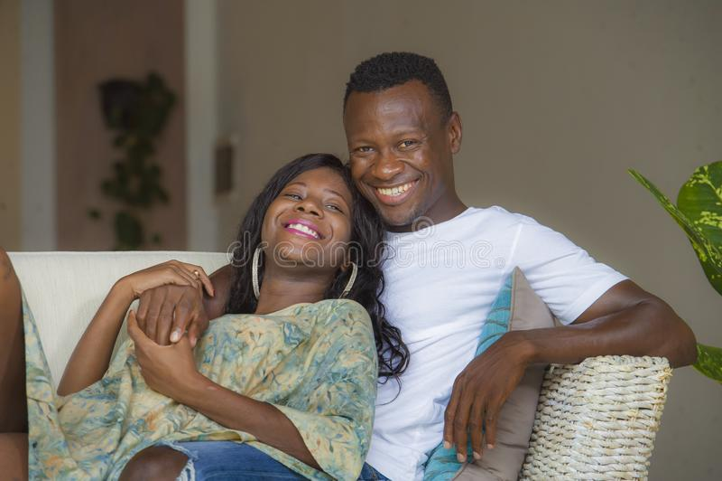 O retrato da casa do estilo de vida de pares afro-americanos românticos felizes e bem sucedidos novos no amor relaxou o assento c fotos de stock