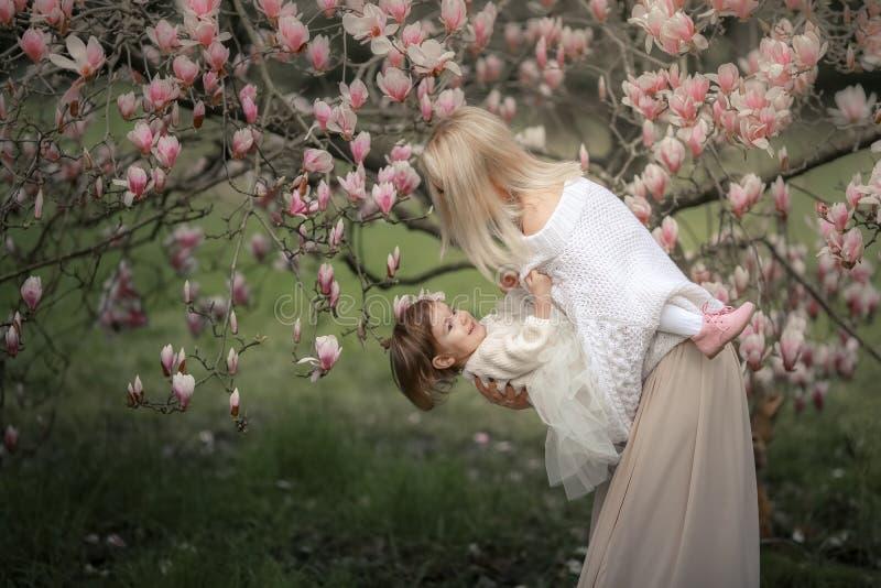 O retrato da criança alegre feliz na roupa branca sobre a árvore floresce o fundo da flor Família que joga junto fora fotografia de stock