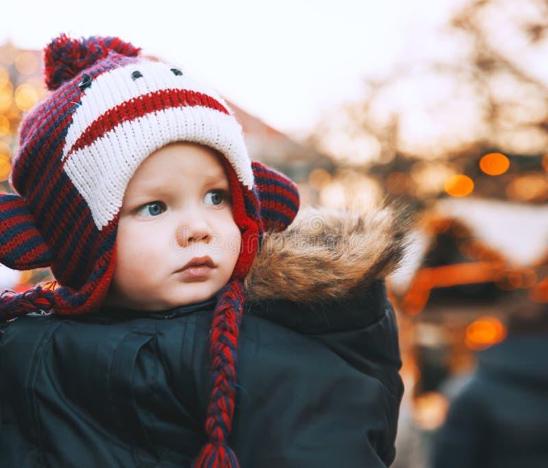O retrato da criança em um chapéu engraçado passa feriados do inverno com fami imagem de stock