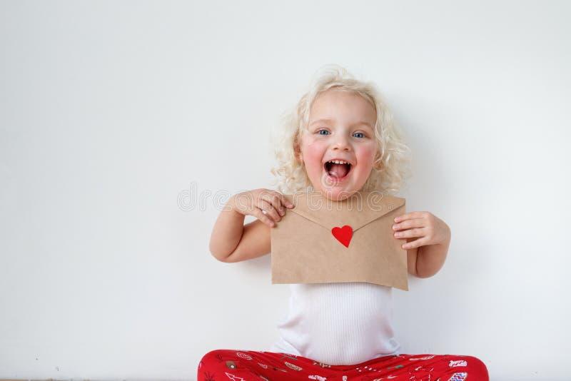 O retrato da criança pequena adorável tem a expressão alegre, guarda a letra a Santa Claus, espera que seus sonhos vêm verdadeiro fotos de stock