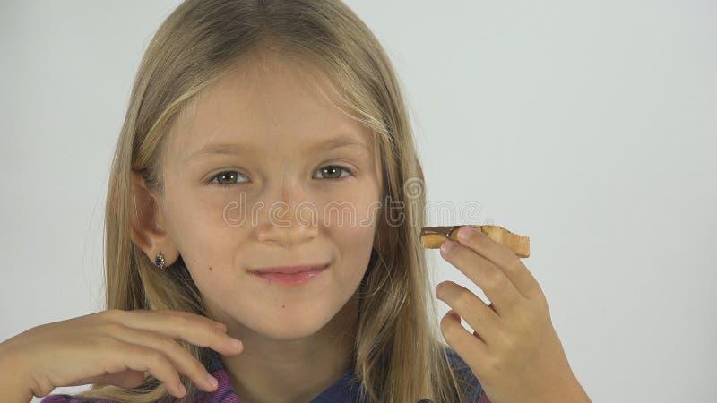 O retrato da criança que come o café da manhã, cara da menina, criança come o brinde e o chocolate 4K fotos de stock