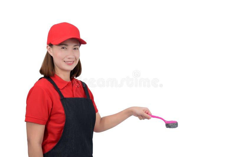 O retrato da empregada nova que sorri no uniforme vermelho com terra arrendada da mão do avental esfrega a escova isolada no back fotos de stock royalty free